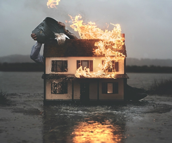 flaming miniature house with bucket of water being poured on it