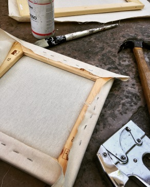 Back of canvas stretched across stretcher bars and tools (hammer, staple gun, gesso) used for stretching canvas