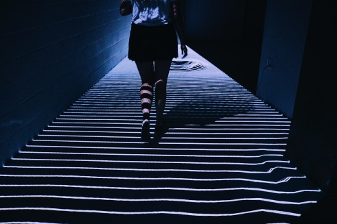 person walking on stripes of light